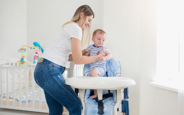Schöne junge mutter, die ihr baby im hochstuhl sitzt