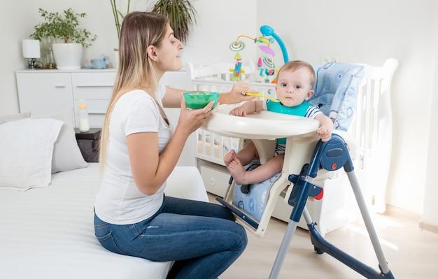 Schöne junge mutter, die ihr baby mit fruchtsauce im hochstuhl füttert