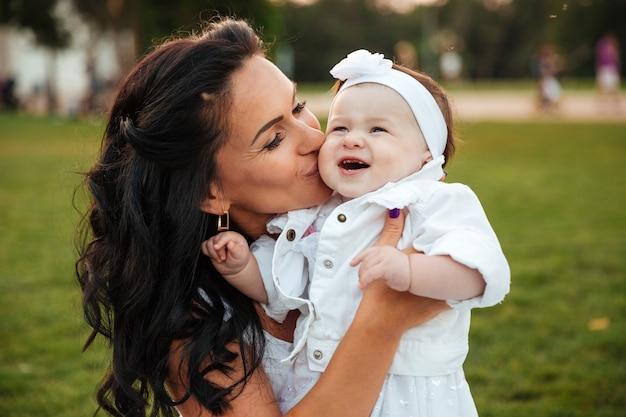 Schöne junge mutter, die ihre kleine tochter im park küsst