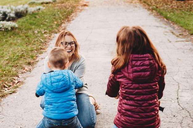 Schöne junge mutter, die lacht, während sie mit ihren kindern draußen spielt.