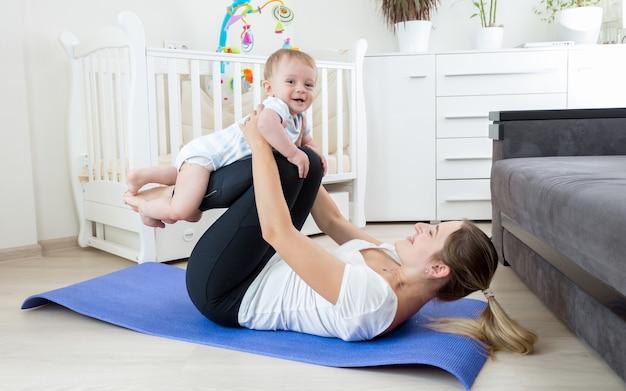 Schöne junge mutter, die yoga mit ihrem baby praktiziert