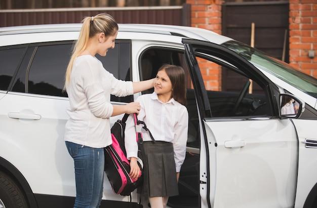 Schöne junge mutter hilft tochter, aus dem auto auszusteigen und die schultasche anzuziehen
