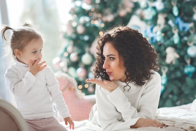 Schöne junge mutter mit ihrer niedlichen kleinen tochter, die weihnachtsferien feiert. glückliche familie, die weihnachtsgeschenke öffnet und einander einen luftkuss schickt
