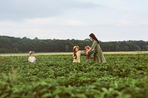 Schöne junge mutter mit kindern in einem leinenkleid mit einem korb erdbeeren sammelt eine neue ernte und hat spaß mit den kindern