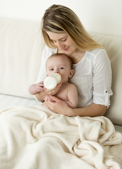 Schöne junge mutter sitzt auf dem bett und füttert ihr baby aus der flasche
