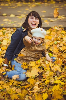 Schöne junge mutter und ihre glückliche tochter haben im herbst spaß im wald. spaziergänge in einem herbstpark mit den kindern. familie, die viel zeit verbringt, zusammen mit gefallenen blättern zu spielen.