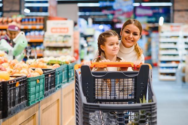 Schöne junge mutter und ihre kleine tochter lächeln und kaufen essen