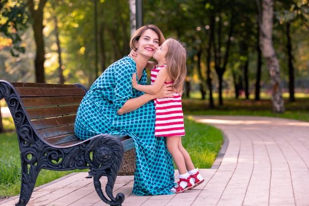 Schöne junge mutter und tochter in warmen sonnigen sommertag. glückliche familie mutter und kind kleine tochter spielen und spazieren im park und genießen die schöne natur.