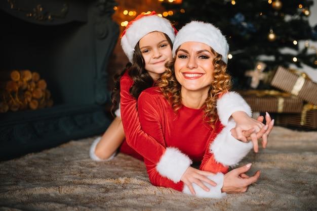Schöne junge mutter und tochter sitzen auf dem boden neben einem weihnachtsbaum und umarmen sich.