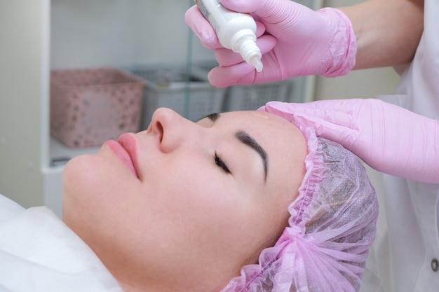 Schöne junge natürliche frau ohne make-up, ein serum wird mit einer pipette auf ihr gesicht aufgetragen.