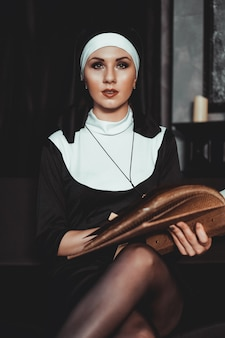 Schöne junge nonne im schwarzen anzug der religion hält bibel und posiert vor der kamera mit großem buch auf einer schwarzen oberfläche