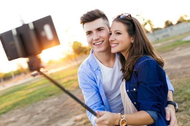 Schöne junge paare, die ein selfie im park nehmen.