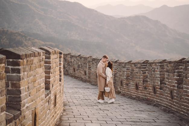 Schöne junge paare, die neigung auf der chinesischen mauer zeigen