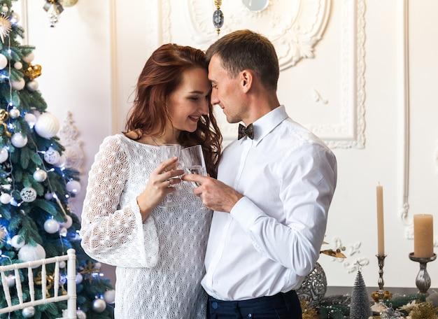 Schöne junge paare, die zu hause weihnachten feiern