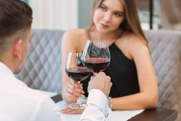 Schöne junge paare mit gläsern rotwein im luxusrestaurant