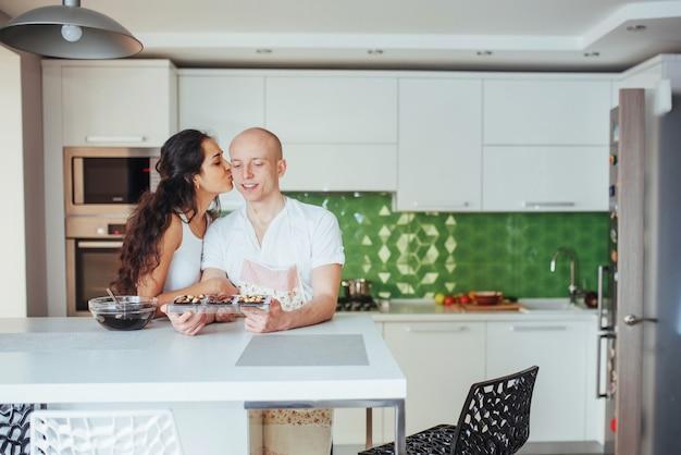 Schöne junge paare stellten das lächeln beim in der küche zu hause kochen grafisch dar.
