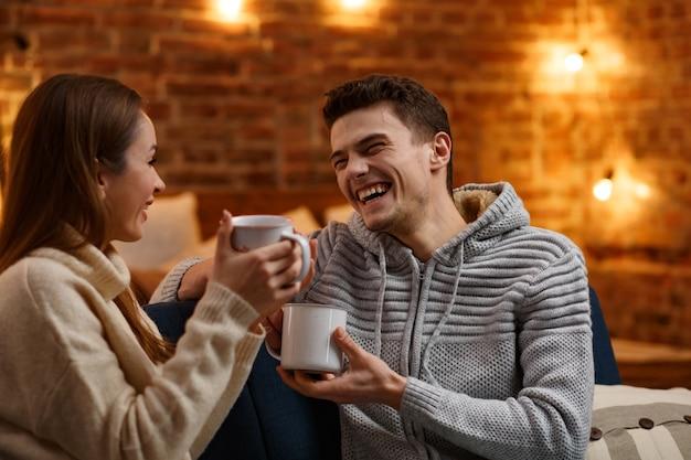 Schöne junge paare zu hause trinken kaffee am weihnachtsmorgen. zeit miteinander verbringen, beziehungen und menschenkonzept. winterferien, weihnachtsfeiern, neujahrskonzept.