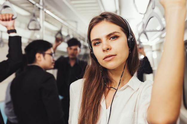 Schöne junge passagierin, die mit kopfhörern und während hemd in der modernen u-bahn steht