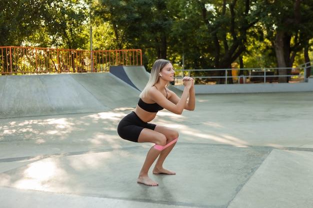 Schöne junge passende frau macht morgengymnastik mit fitness-gummibändern im freien.