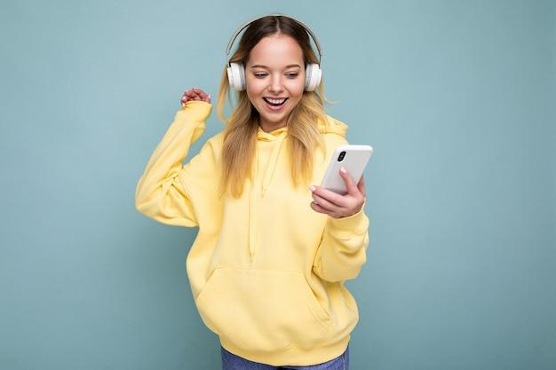 Schöne junge positive blonde frau mit gelbem stylischem hoodie auf blauem hintergrund isoliert