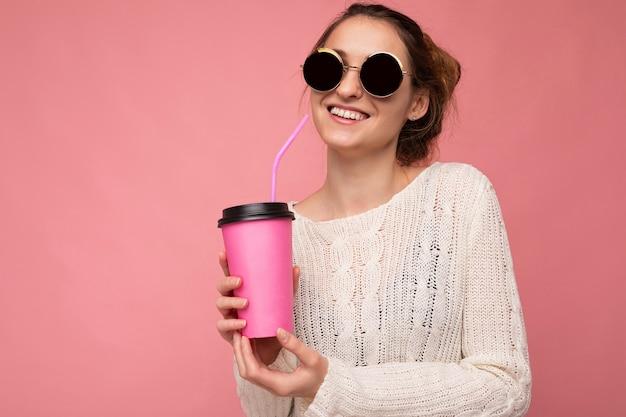Schöne junge positive brünette frau, die lässige, stilvolle kleidung trägt, die über einer bunten hintergrundwand isoliert ist, die pappbecher für das modell hält, das kaffee trinkt und in die kamera schaut