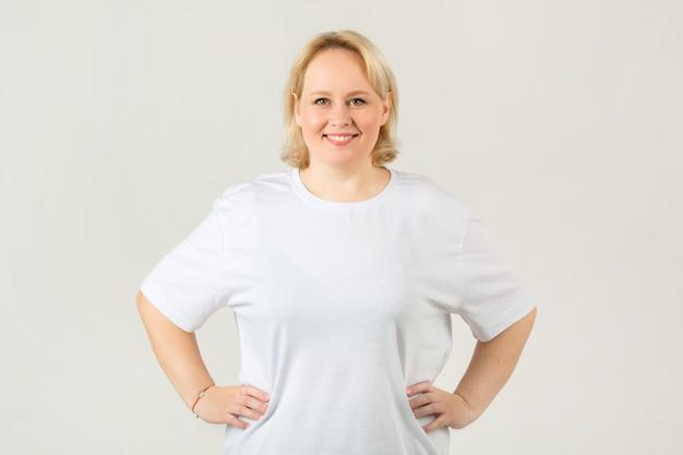Schöne junge pralle frau in einem weißen t-shirt auf einem weißen hintergrund