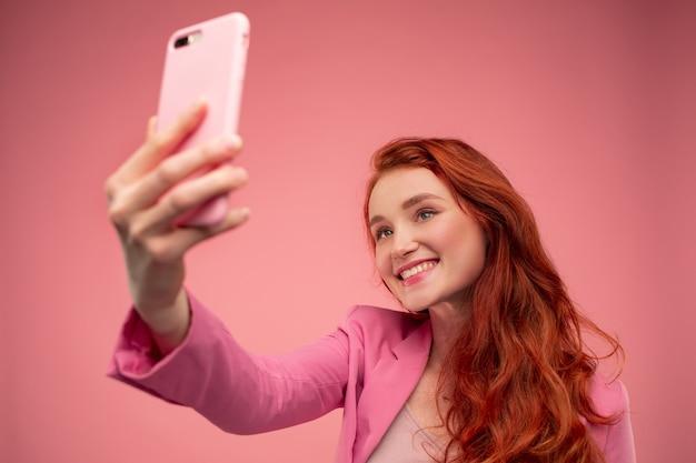 Schöne junge rothaarige frau, die selfie macht