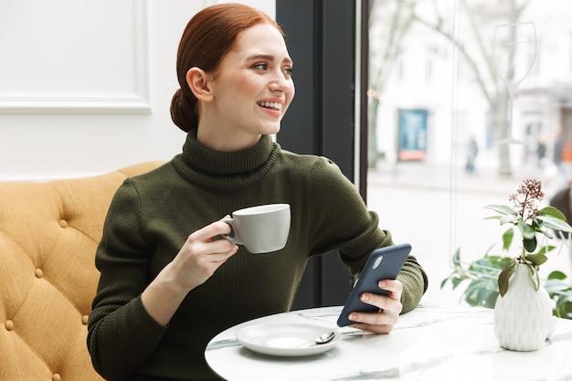Schöne junge rothaarige frau, die sich am café-tisch drinnen entspannt, kaffee trinkt, handy benutzt