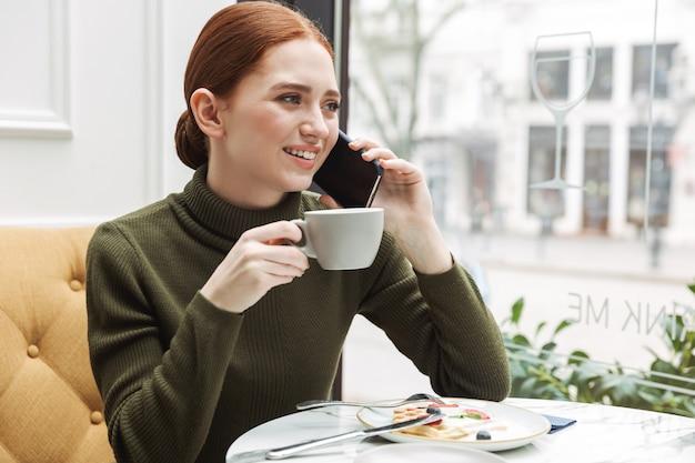 Schöne junge rothaarige frau, die sich am café-tisch drinnen entspannt, zu mittag isst, mit dem handy spricht