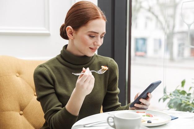 Schöne junge rothaarige frau, die sich am café-tisch drinnen entspannt, zu mittag isst, mit handy