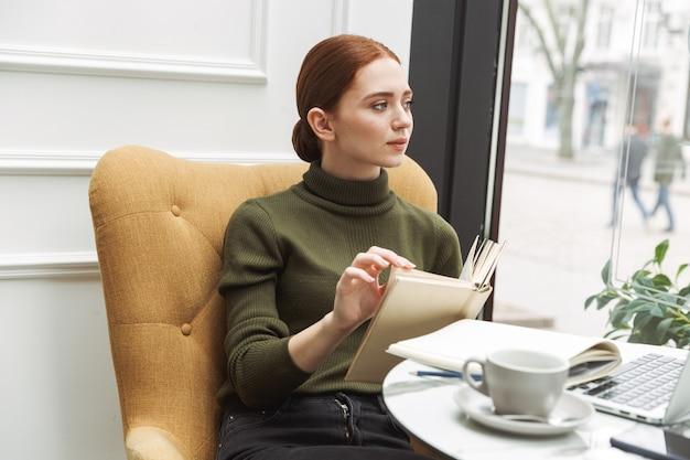 Schöne junge rothaarige frau, die sich drinnen am café-tisch entspannt, kaffee trinkt, ein buch liest?