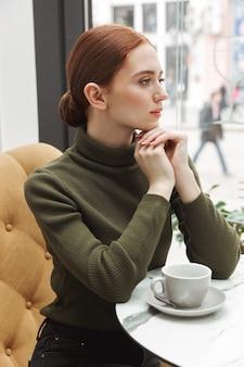 Schöne junge rothaarige frau, die sich drinnen am café-tisch entspannt und kaffee trinkt