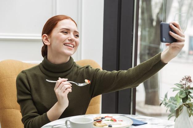 Schöne junge rothaarige frau, die sich drinnen am café-tisch entspannt, zu mittag isst und ein selfie macht