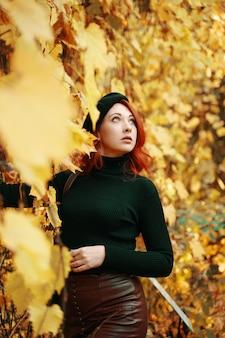 Schöne junge rothaarige frau im stilvollen modell des herbstparks unter gelbem trockenem laub der bäume ehrfürchtig...