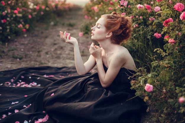 Schöne junge rothaarige frau in einem schwarzen kleid in einem rosengarten.