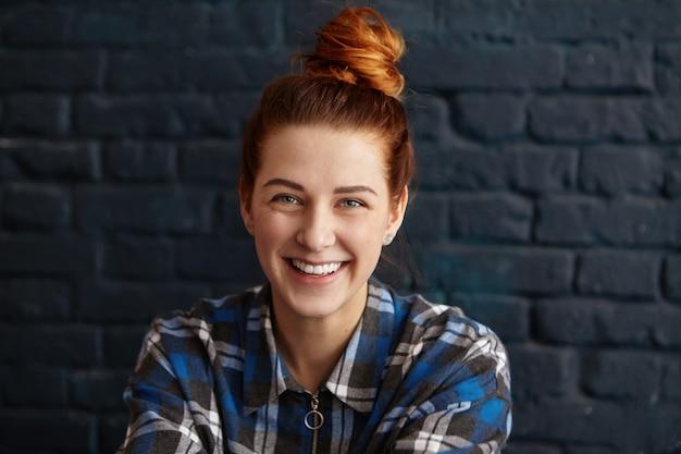 Schöne junge rothaarige frau mit haarknoten, die blaues kariertes hemd trägt, das mit niedlichem glücklichem lächeln schaut