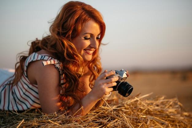 Schöne junge rothaarige frau mit weinlesekamera in einem feld bei sonnenuntergang, kamera betrachtend, lächelnd, selektiver fokus