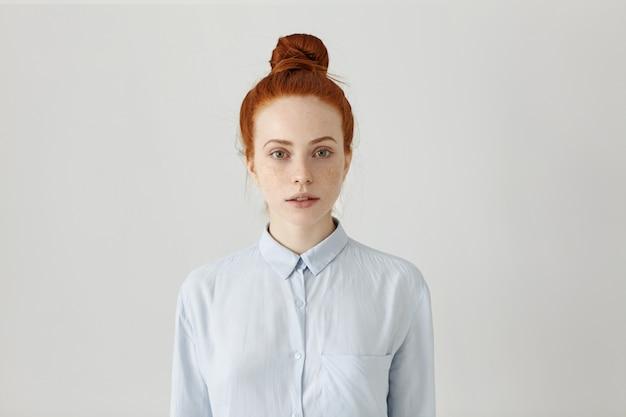 Schöne junge rothaarige weibliche angestellte mit haarknoten posiert drinnen gekleidet in hellblauem formellem hemd, bereitet sich auf arbeit vor, hat ernstes aussehen. horizontaler, isolierter schuss