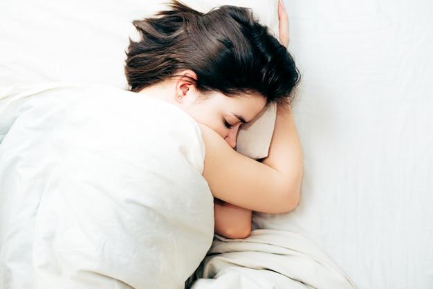 Schöne junge schlafende frau beim lügen in ihrer draufsicht des betts