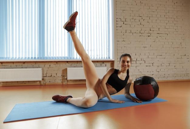 Schöne junge schlanke frau, die einige gymnastik an der turnhalle mit medball tut. sportler, sport, seil, training, training, übungen und konzept für einen gesunden lebensstil