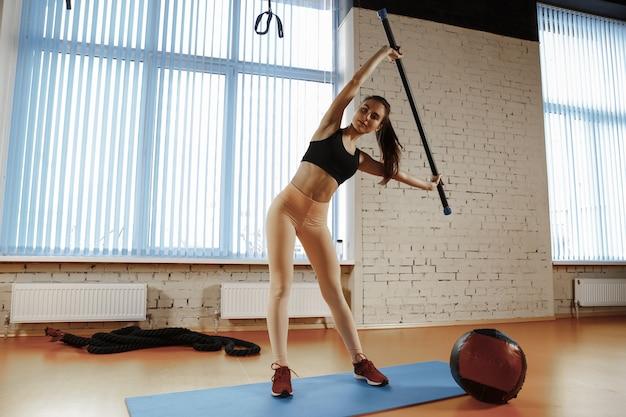 Schöne junge schlanke frau, die einige gymnastik an der turnhalle tut. sportler, sport, seil, training, training, übungen und konzept für einen gesunden lebensstil