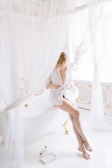 Schöne junge schlanke frau in einem hemd am morgen in einem hellen raum neben einem weißen bad mit goldbeschlägen.