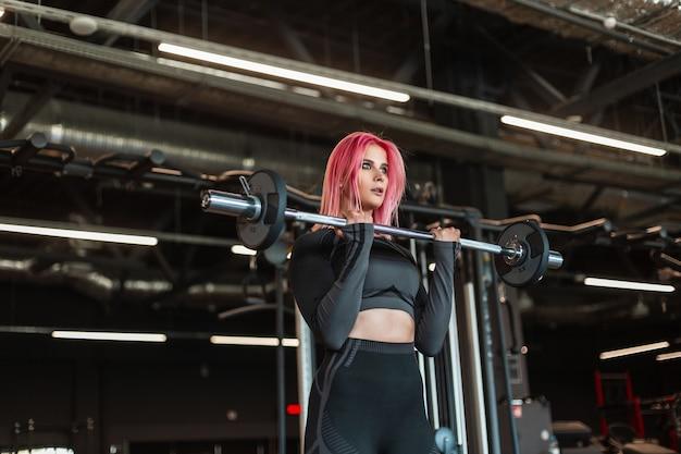 Schöne junge schlanke frau in schwarzer modischer sportbekleidung, die mit einer langhantel und platten im fitnessstudio trainiert
