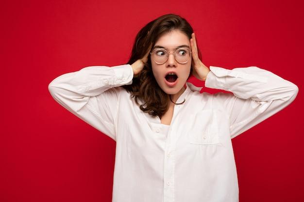Schöne junge schockierte überraschte lockige brünette frau mit weißem hemd und optischer brille isoliert