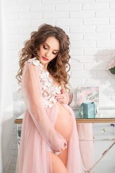 Schöne junge schwangere dame in einem rosa kleid zu hause