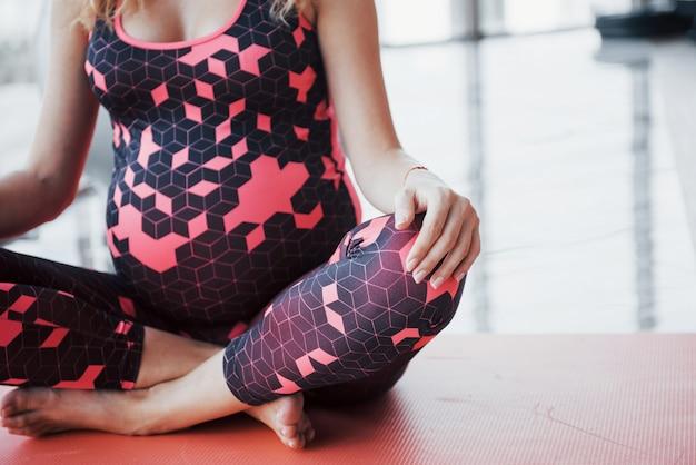Schöne junge schwangere frau, die in der halle meditiert.