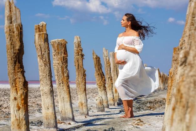 Schöne junge schwangere frau, die in der natur auf salzsee steht.