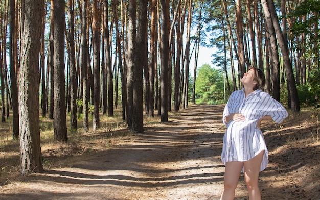 Schöne junge schwangere frau, die tief draußen im park atmet