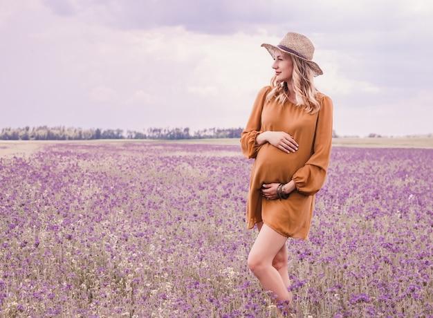 Schöne junge schwangere frau im hut auf dem lavendelgebiet. blühende blumen