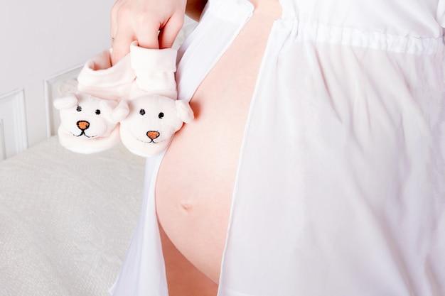 Schöne junge schwangere frau, jugendlicher in der weißen unterwäsche mit den stiefeln des babys symbolisiert die aufwartung eines kindes